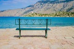 Metal zieleni ławka na nabrzeżu z morzem i widokiem górskim zdjęcie stock