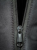 Metal zipper on black synthetic fabric Stock Photo