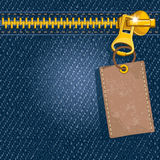 Metal zipper on denim background. Metal zipper with label on denim background Royalty Free Stock Images