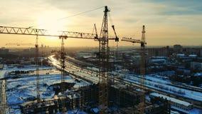 Metali żurawie pracują na miejscu, buduje budynek blisko drogi zbiory wideo