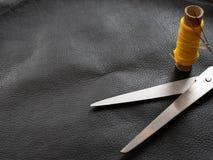 Metali błyszczący nożyce z zwitki nicią na czarnej skórze fotografia stock