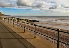 Metali poręcze na Sidmouth esplanadzie, zatrzymywać ludzi spadać dalej otoczak plaża pod niektóre 3 metres obrazy stock