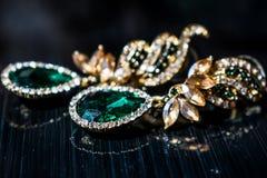 Metali złociści kolczyki z zielenią, rhinestones, szmaragdowymi kamieni, bielu i koloru żółtego, Na czarnym glansowanym tle zdjęcie stock
