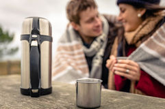 Metalic cup and thermos outdoors with couple Royalty Free Stock Photos