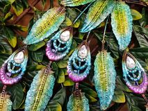 Metalic jewellery inspiration. Colorfull metalic decoration on agains green leaves Royalty Free Stock Images
