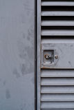 Metalic Locked Door. Slotted metal door with a lock and handle next to matte gray metal wall Royalty Free Stock Photos