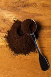 Metalic spoon and coffee. Over wooden surface Stock Photos