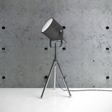 Metalic tripod lamp and concrete wall in empty room Royalty Free Stock Photography