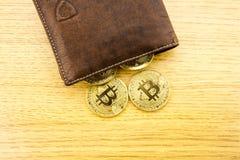 Metall-bitcoins in der braunen ledernen Geldbörse Bitcoin - modernes virtuelles Abbildung 3D Stockfotos