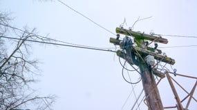 Metall den wood elektriska polen, elkraft fodrar pylonen, maktlättheter, dålig trådmontering royaltyfri bild