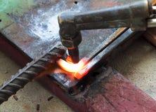 Metall för cutting för gasuppvärmning som böjer den fyrkantiga stången arkivfoto