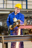 Metall för stålbyggnadsarbetareklipp med vinkelmolar Royaltyfri Bild