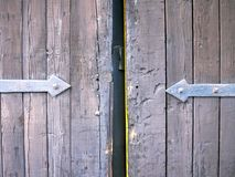 Metall förser med gångjärn med en form av en pil som pekar i motsatt riktning över ett gammalt trädörrutrymme för att förlägga te royaltyfria foton
