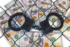 Metall fesselt auf dem Hintergrund von Dollar unter Drahtgeflecht mit Handschellen (Gitter) Stockfoto