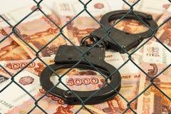 Metall fesselt auf dem Hintergrund von russischen Rubeln unter Drahtgeflecht mit Handschellen (Gitter) Stockfotografie