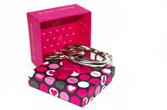 Metall fesselt mit der Geschenkbox mit Handschellen, die auf dem weißen Hintergrund lokalisiert wird Lizenzfreies Stockfoto