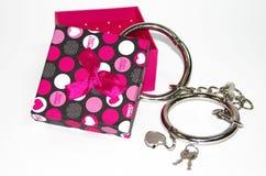 Metall fesselt mit der Geschenkbox mit Handschellen, die auf dem weißen Hintergrund lokalisiert wird Stockfoto