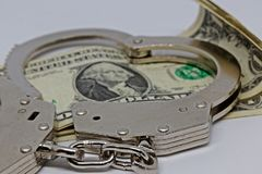Metall handcuffs and money. Dollar notes and metall cuffs royalty free stock photo