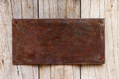 Metall har den dekorativa plattan för rost på trä Arkivfoto