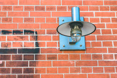 Metall lamp fixed on a brick wall Royalty Free Stock Image