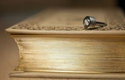 Metall mynt-pläterad detalj av en tappningkamera som ligger på den gamla boken med en guld- kant fotografering för bildbyråer