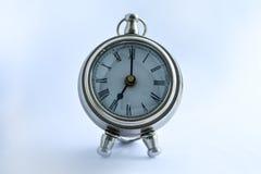 Metall och den skinande klockan stiliserade antikviteten på en tabell på en ljus bakgrund fotografering för bildbyråer
