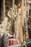 Metall- och mässingskoskällor som hänger i en medeltida stall Royaltyfri Bild