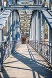 Metall och träbro över en flod på en solig dag Arkivfoton