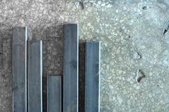 Metall profilerade rör ligger på det konkreta golvet som en graf fotografering för bildbyråer