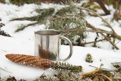 Metall rånar av varmt te i snö Varm drink på en frostig dag Arkivbild