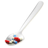 Metall spoon with a portion of medicine isolated Stock Photo