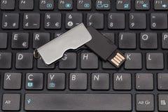 Metall-USB-Blitz-Antrieb auf einer schwarzen Tastatur Stockbilder