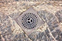 Metallabfluß auf typischem Steinpflasterung Andalusian Stockbilder