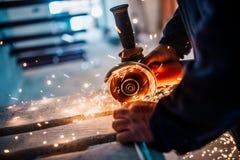 Metallarbeiter, der Eisen und Metall mit einem elektrischen Drehwinkelschleifer und -c$arbeiten, Metallfunken erzeugend schneidet stockbild