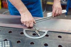 Metallarbeiter, der Zollstock verwendet, Stahlstreifen zu messen stockfotos