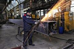 Metallarbeitskraftschleifen schweißt Stahlprofile unter Verwendung eines Winkelschleifers Stockfotos