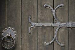Metallarbete för Wrought järn på aldträdörr Royaltyfri Fotografi