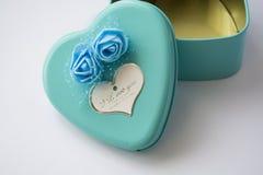 Metallasken i form av hjärta med inskriften 'älskar jag dig 'och med rosor Blått färgar St Dag för valentin` s royaltyfria foton