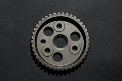 Metallautozahnrad auf schwarzem Hintergrund stockbild