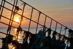 Metallbau mit Plastikabfall im vorderen Meer bei Sonnenuntergang lizenzfreies stockbild