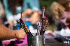 Metallbehållare mycket av målarpenslar, medan ungar sitter utanför arkivfoton