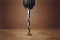 Metallbohrer macht ein Loch in einem Stück Holz Lizenzfreie Stockbilder