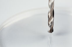 Metallbohrer macht ein Loch in einem Stück Plastik Stockfotos