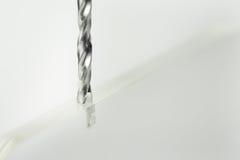Metallbohrer macht ein Loch in einem Stück transparentem Plastik Stockbilder