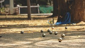 Metallbollar och orange träboll på jordningen i hemträdgård - spela Petanque i en Sunny Day Arkivfoton