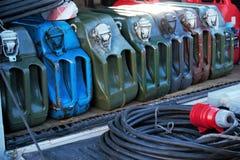 Metallbränslebensindunkar och maktextander Färgrika kanistrar för lagra och trans.bränsle arkivfoton