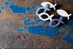 Metallchristliche Fischformen auf hölzernem Hintergrund stockfotos