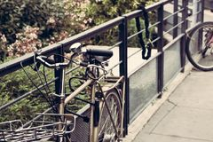 Metallcykel som hänger på ett staket arkivfoto