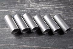 Metallcylindrar på mörk bakgrund Fotografering för Bildbyråer