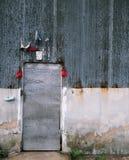 Metalldörr på den rostiga väggen Arkivbild